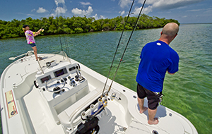 two anglers on a Yellowfin Bay boat fishing near a mangrove island.