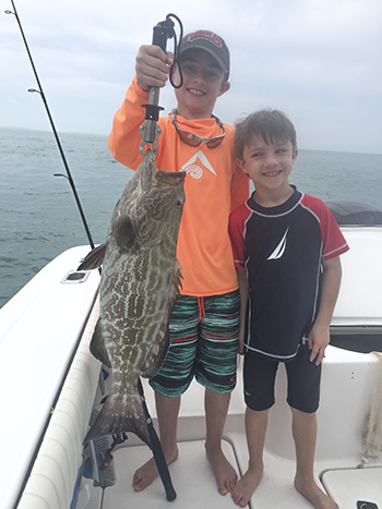 Kids with thier fish. Two young men with a grouper they caught here in Key West on a Family Fun Fishing Charter