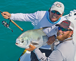 two fishermen holding up a permit that they caught on a Key West wreck