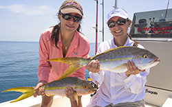 two ladies holding up a pair of yellowtail snappers