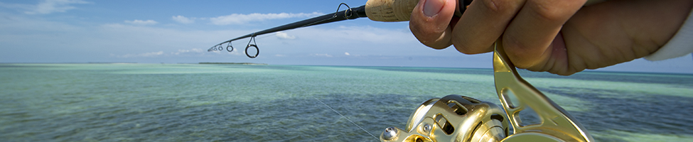 fishing the flats off of Key West. A fishign reel being held up over pretty water.
